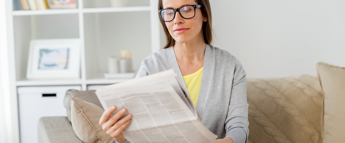 woman in glasses reading newspaper at home