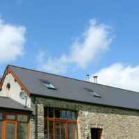 Newly restored residential stone barn with a slate roof in rural countryside against a blue sky with clouds.